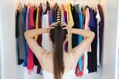 Mulher confusa que escolhe que vestir na frente de seu vestuário imagens de stock royalty free
