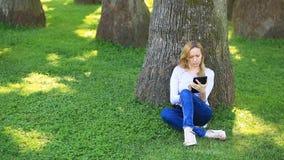 Mulher considerável que senta-se sob uma palmeira e que consulta o Internet em um smartphone vídeos de arquivo