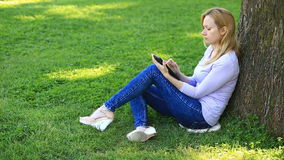 Mulher considerável que senta-se sob uma palmeira e que consulta o Internet em um smartphone video estoque