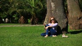 Mulher considerável que senta-se sob uma palmeira e que consulta o Internet em um smartphone filme