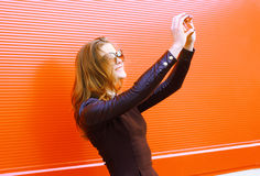 A mulher consideravelmente à moda faz o autorretrato no smartphone Imagem de Stock