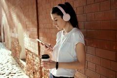 A mulher consideravelmente caucasiano dos jovens com o copo esperto do telefone e de café em suas mãos está a parede de tijolo pr fotos de stock royalty free