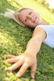 Mulher consideravelmente caucasiano que coloca na grama ao ar livre fotos de stock