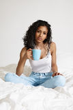 Mulher consideravelmente latin com um café na cama branca imagens de stock royalty free