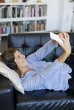 Mulher consideravelmente longa do cabelo dos jovens que encontra-se em um sofá que faz a selfie sobre o imagens de stock royalty free