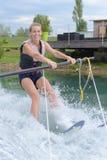 Mulher consideravelmente loura dos jovens que aprende montar o wakeboard Imagens de Stock