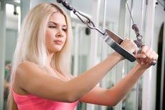 Mulher consideravelmente loura que exercita na estação do pulldown Fotografia de Stock Royalty Free