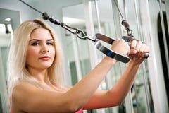 Mulher consideravelmente loura que exercita na estação do pulldown Imagens de Stock