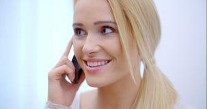 Mulher consideravelmente loura que fala em seu móbil video estoque