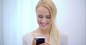 Mulher consideravelmente loura que texting em seu móbil video estoque