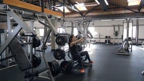 A mulher consideravelmente magro dos jovens exercita a borboleta na máquina no gym filme