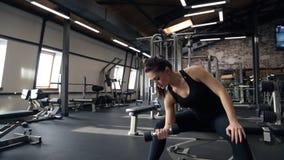 A mulher consideravelmente magro dos jovens exercita com peso no gym video estoque