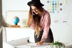 Mulher consideravelmente nova do arquiteto que trabalha no modelos ao falar no telefone no escritório fotografia de stock royalty free