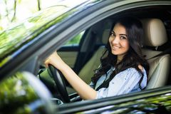 Mulher consideravelmente nova que conduz seu carro novo Carro da movimentação de Womanm na cidade foto de stock