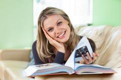 Mulher consideravelmente nova que encontra-se em um sofá que lê um livro Imagens de Stock