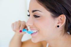 Mulher consideravelmente nova que escova seus dentes Foto de Stock