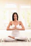 Mulher consideravelmente nova que faz a meditação da ioga Imagens de Stock