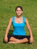 Mulher consideravelmente nova que meditating na grama Fotos de Stock Royalty Free