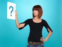 Mulher consideravelmente nova que mostra um ponto de interrogação Fotos de Stock