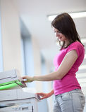 Mulher consideravelmente nova que usa uma máquina da cópia Imagem de Stock