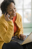 Mulher consideravelmente preta no telefone e no portátil de pilha Imagens de Stock