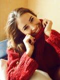 Mulher consideravelmente real dos jovens na camiseta e no lenço por todo o lado em sua cara que sorri em casa, positivo do invern foto de stock