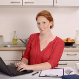 Mulher consideravelmente ruivo que trabalha em seu escritório domiciliário Foto de Stock Royalty Free