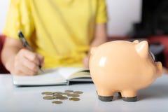 A mulher conta a moeda no piggybank foto de stock