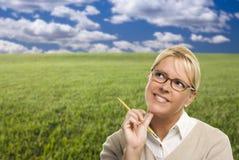 Mulher contemplativa no campo de grama que olha acima e sobre Imagem de Stock