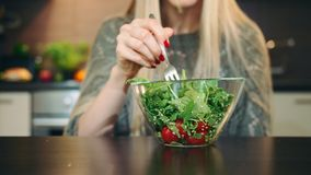 Mulher contente que come a salada saudável Fêmea nova bonita que aprecia a salada vegetal saudável e que olha a câmera quando filme