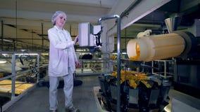 A mulher controla uma máquina de trabalho em uma planta de produção alimentar, movimento lento video estoque