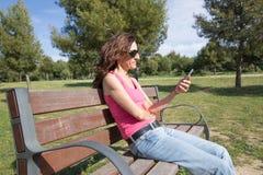 Mulher cor-de-rosa da camisa com assento móvel no parque Fotografia de Stock