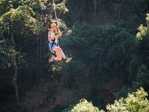 A mulher corajoso no capacete e o chicote de fios fecham o forro no parque da aventura Imagens de Stock