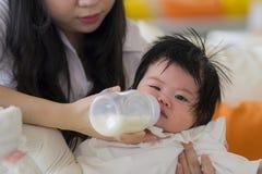 Mulher coreana asiática bonito que alimenta seu bebê doce com assento da garrafa de leite no recurso de feriados que aprecia féri imagens de stock royalty free