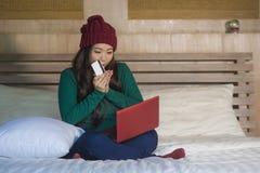 Mulher coreana asiática feliz bonita nova no chapéu do inverno relaxado no cartão de crédito da terra arrendada da cama usando o  fotos de stock