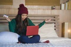 Mulher coreana asiática feliz bonita nova no chapéu do inverno relaxado no cartão de crédito da terra arrendada da cama usando o  fotos de stock royalty free