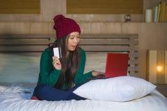 Mulher coreana asiática feliz bonita nova no chapéu do inverno relaxado no cartão de crédito da terra arrendada da cama usando o  fotografia de stock royalty free