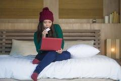 Mulher coreana asiática feliz bonita nova no chapéu do inverno relaxado no cartão de crédito da terra arrendada da cama usando o  imagens de stock