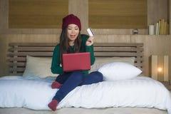 Mulher coreana asiática feliz bonita nova no chapéu do inverno relaxado no cartão de crédito da terra arrendada da cama usando o  imagem de stock royalty free