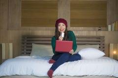 Mulher coreana asiática feliz bonita nova no chapéu do inverno relaxado no cartão de crédito da terra arrendada da cama usando o  foto de stock