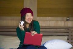 Mulher coreana asiática feliz bonita nova no chapéu do inverno relaxado no cartão de crédito da terra arrendada da cama usando o  fotografia de stock