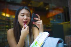Mulher coreana asiática feliz e atrativa nova do turista que senta-se na cafetaria da cidade usando a composição do batom e o wa  foto de stock