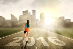 A mulher corre na estrada com números 2016 Fotografia de Stock Royalty Free