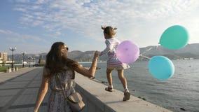 A mulher corre pela mão com uma menina bonita pequena na manhã no beira-mar da cidade video estoque
