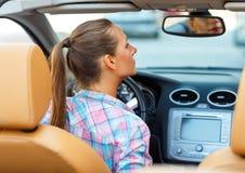 A mulher corrige a composição que olha no espelho de rearview em um conver Foto de Stock