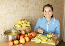 A mulher corta maçãs para o atolamento da maçã Imagens de Stock