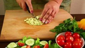 A mulher corta o abacate, descascado de sua casca com uma faca, para fazer uma salada Close-up video estoque