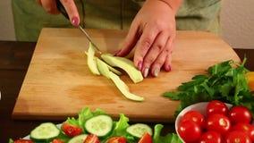 A mulher corta o abacate, descascado de sua casca, em partes pequenas com uma faca Close-up vídeos de arquivo