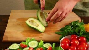 A mulher corta o abacate em partes pequenas Close-up vídeos de arquivo