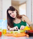 A mulher corta o aipo verde na cozinha Imagem de Stock
